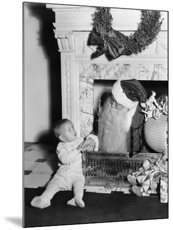 Santa Claus with a Little Boy in Front of a Fireplace--Mounted Photo