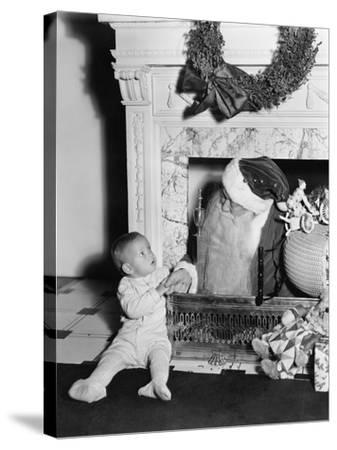 Santa Claus with a Little Boy in Front of a Fireplace--Stretched Canvas Print