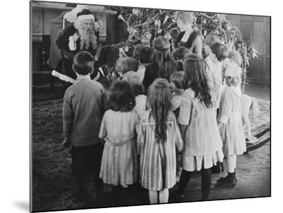 Santa Claus Visiting with Large Group of Children--Mounted Photo