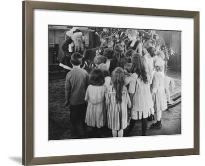 Santa Claus Visiting with Large Group of Children--Framed Photo
