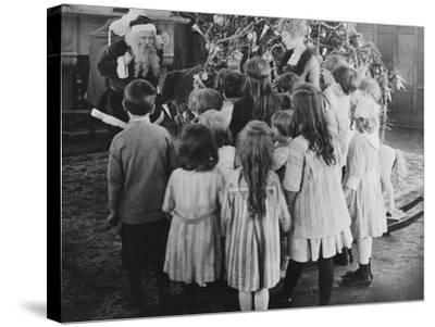Santa Claus Visiting with Large Group of Children--Stretched Canvas Print