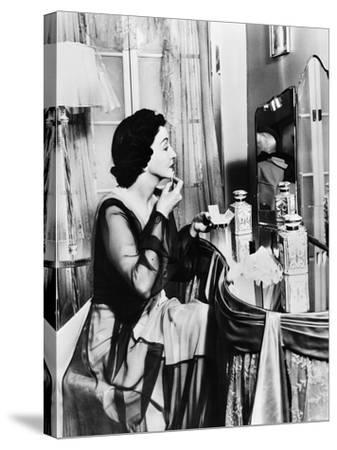 Young Woman Looking into a Mirror and Putting on Make Up--Stretched Canvas Print