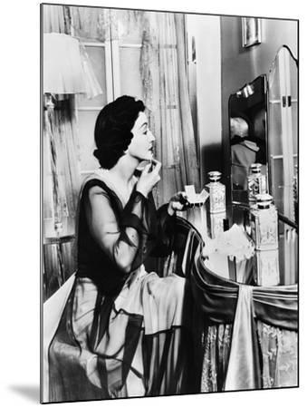 Young Woman Looking into a Mirror and Putting on Make Up--Mounted Photo