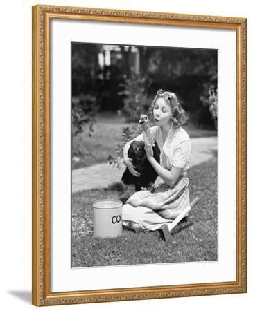 Young Woman, with an Ax Next to Her, Hugs a Turkey--Framed Photo