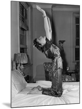 Woman Stretching on Bed--Mounted Photo