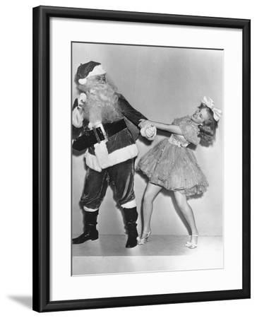 Woman Trying to Dance with Santa Claus--Framed Photo