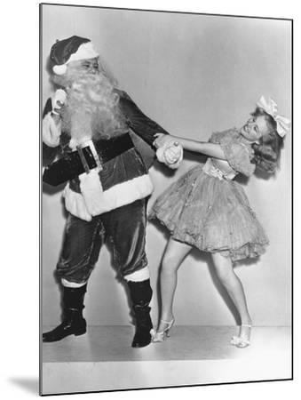 Woman Trying to Dance with Santa Claus--Mounted Photo