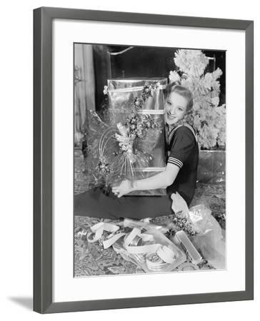 Young Woman Sitting in a Living Room Hugging a Present on Christmas Day--Framed Photo