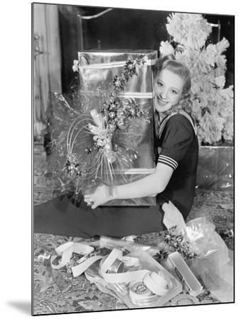 Young Woman Sitting in a Living Room Hugging a Present on Christmas Day--Mounted Photo