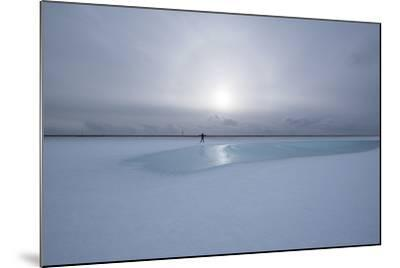 Lonely Person in Icelandic Lowlands with Blue Puddle of Water and Sun in the Background, Winter-Niki Haselwanter-Mounted Photographic Print