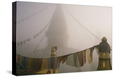 A temple and prayer flags shrouded in fog.-David Edwards-Stretched Canvas Print