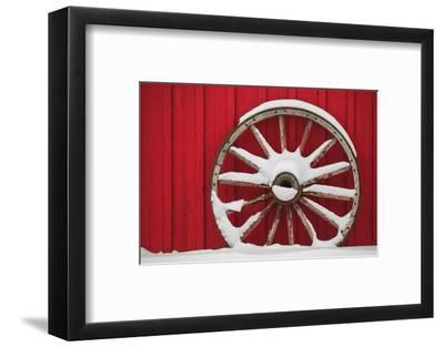 Snow-covered wagon wheels against red barn near town of Banff, Canadian Rockies, Alberta, Canada-Stuart Westmorland-Framed Photographic Print