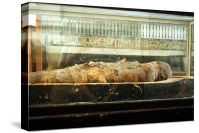 Mummy wrapped in bandages and lying on the base of a coffin, Ancient Egyptian. Artist: Unknown-Unknown-Stretched Canvas Print