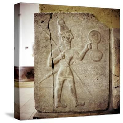 Hittite relef of a Hittite warrior or war-god with shield spear and sword. Artist: Unknown-Unknown-Stretched Canvas Print