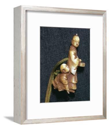 Japanese Netsuke of a man and boy at new year, 19th century. Artist: Unknown-Unknown-Framed Giclee Print