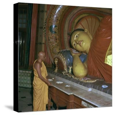 Buddhist priest before the image of a reclining Buddha. Artist: Unknown-Unknown-Stretched Canvas Print