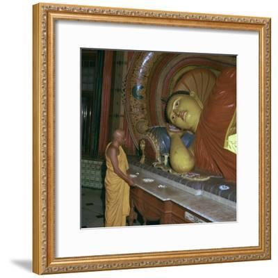 Buddhist priest before the image of a reclining Buddha. Artist: Unknown-Unknown-Framed Photographic Print