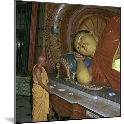Buddhist priest before the image of a reclining Buddha. Artist: Unknown-Unknown-Mounted Photographic Print