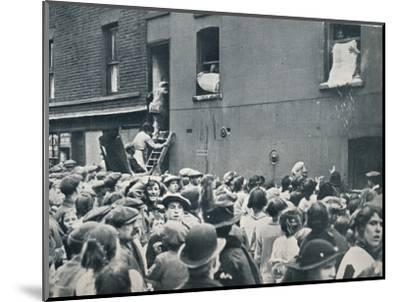 Crowd watching the looting of a German house in Poplar, c1914-Unknown-Mounted Photographic Print