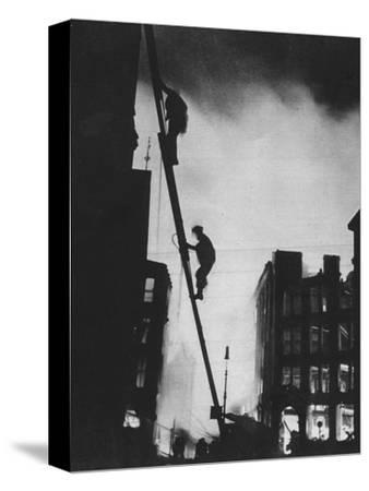 'Out in the Blitz, silhouetted aganinst the light of fires, rescue men climb into a building in St-Unknown-Stretched Canvas Print