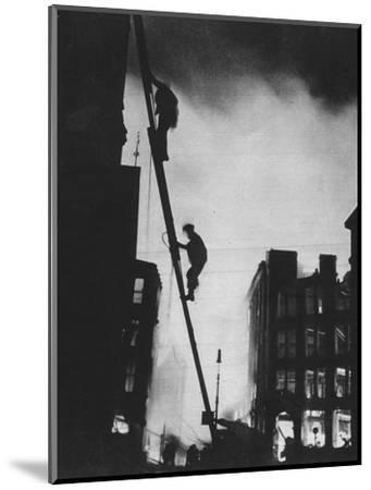'Out in the Blitz, silhouetted aganinst the light of fires, rescue men climb into a building in St-Unknown-Mounted Photographic Print