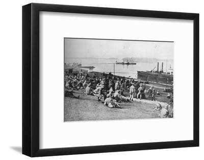 ''Austrian prisoners taken by Serbians resting at mid-day on the banks of the Danube', 1915-Unknown-Framed Photographic Print
