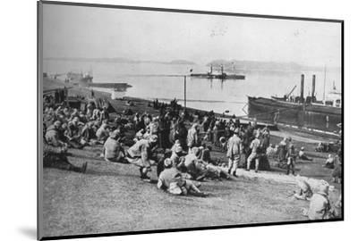 ''Austrian prisoners taken by Serbians resting at mid-day on the banks of the Danube', 1915-Unknown-Mounted Photographic Print