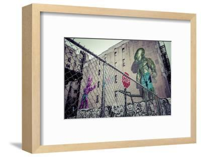 Backyard scene Graffiti of a pink and green superpower baby, Little Italy, Manhattan, New York, USA-Andrea Lang-Framed Photographic Print