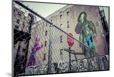 Backyard scene Graffiti of a pink and green superpower baby, Little Italy, Manhattan, New York, USA-Andrea Lang-Mounted Photographic Print