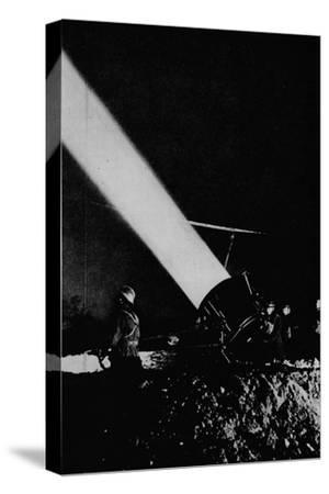 Elephant's child. A searchlight of 210,000,000 candle-power probes the night sky with its beam, 1-Unknown-Stretched Canvas Print