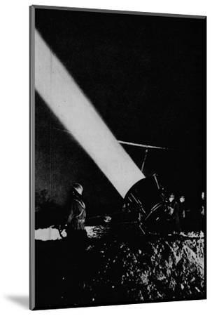 Elephant's child. A searchlight of 210,000,000 candle-power probes the night sky with its beam, 1-Unknown-Mounted Photographic Print