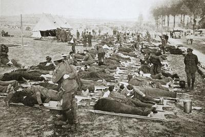Wounded men waiting to be taken away to a clearing station, France, World War I, 1916-Unknown-Framed Photographic Print