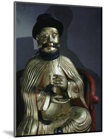 Gilt statue of Marco Polo holding a pomegranate, symbol of wealth and prosperity-Werner Forman-Mounted Photographic Print