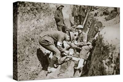 Red Cross men in the trenches tend a wounded man, Somme campaign, France, World War I, 1916-Unknown-Stretched Canvas Print