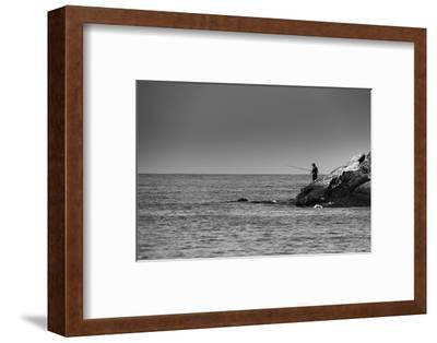 Black and White shot of a lone fisherman on rocks at the beach--Framed Photo