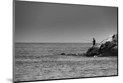 Black and White shot of a lone fisherman on rocks at the beach--Mounted Photo