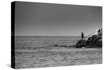 Black and White shot of a lone fisherman on rocks at the beach--Stretched Canvas Print