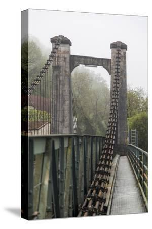 France, Cajarc. Early morning fog on the iron bridge over the Lot River.-Hollice Looney-Stretched Canvas Print