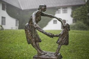 A Sculpture of a Woman and Child Dancing, on a Rainy Day by Ulla Lohmann
