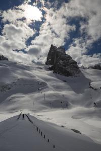 A Skier at the Col Di Bousc and the Snow Covered Dam at the Lago Di Fedaia by Ulla Lohmann