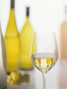 A Glass of White Wine and Wine Bottles in Background by Ulrike Koeb