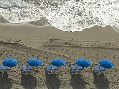 https://imgc.artprintimages.com/img/print/umbrellas-on-a-beach-with-approaching-surf-at-sunrise_u-l-petm950.jpg?p=0