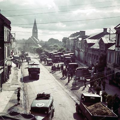 United States Army Trucks, Jeeps and Other Vehicles Entering a Town in Normandy, France, June 1944--Photographic Print