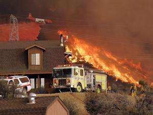 US Forest Service Air Tanker Drops Fire Retardant as the Fire Burns in the Hills Above a Home