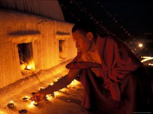 Monk Lighting Butter Lamps at Boudnath, Kathmandu, Nepal by Vassi Koutsaftis