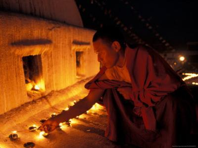 Monk Lighting Butter Lamps at Boudnath, Kathmandu, Nepal