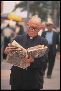 Episcopalian Priest Reading a Newspaper While Walking in Street, New York City by Vernon Merritt III