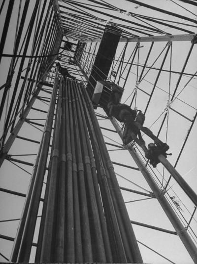 Vertical View of Oil Rig Showing Stacked Drill Pipes and Derrick Man at Work--Photographic Print