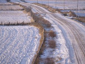View of a Rural Country Road Covered in Snow Next to Farmland