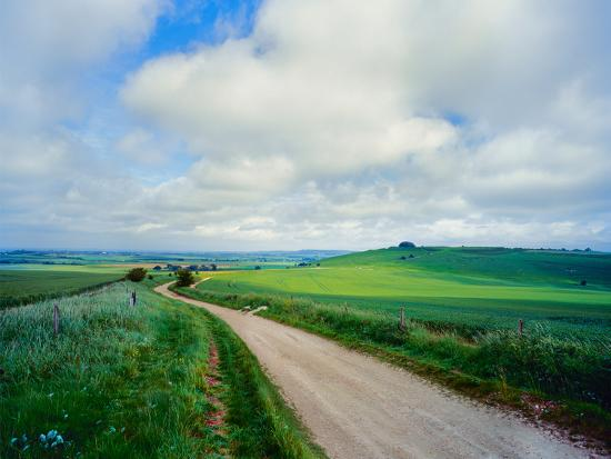 View of road passing through a field, United Kingdom--Photographic Print